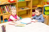stock photo of little kids  - Two little kids drawing with colorful pencils in preschool at the table - JPG