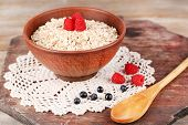 Big round bowl with oatmeal and berries on a lace napkin on a wooden stand
