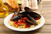 Tasty noodles with mussels on table, close up