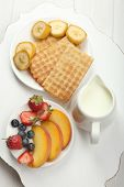 Delicious breakfast with milk, cookies and fruits