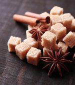 Brown sugar cubes and reed sugar, spices on wooden background