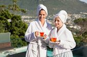 Two smiling young women in bathrobes having tea against view