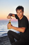 Teenager Boy Opens Beer Bottler On Stone Seacoast In Evening