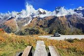 Snow-capped Alps in beautiful autumn day. Table and benches for picnic on the side of the  road. Gr