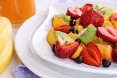 Fresh fruits salad on plate on napkin close up