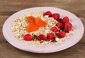 Big plate of oatmeal and berries on wooden background