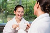 Two smiling young women in bathrobes having tea