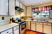Simple Kitchen Interior With Steel Stove And White Cabinets
