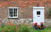 House Front With Red Poppy Flowers And Geraniums