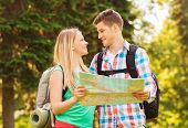 travel, vacation, tourism and friendship concept - smiling couple with map and backpacks looking at