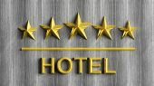 Five golden stars and word Hotel on grey wood