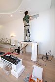 Worker installs a metal plate for fixing the air conditioner
