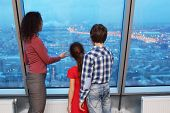 Mother shows children evening cityscape by a large window