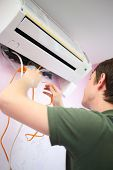 Young worker inserts an orange water pump in air conditioning