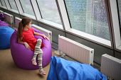 Little girl sitting on the ottoman and looking in large window on a rainy day