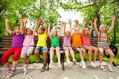 Funny group of kids on bench with arms up