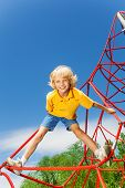 Active boy stands on red rope with legs apart