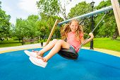 Girl holding chains of swings and swinging
