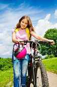 Smiling girl with long hair holds her bike