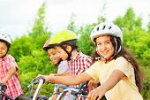 Small cute girl in helmet holds bike handle-bar