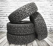 Stack of four new black tyres for winter car on  wooden floor in vintage room with brick wall backgr