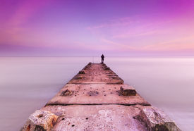 stock photo of jetties  - A concrete and stone jetty reaches out to the sunset sky through calm seas on Bournemouth Beach - JPG