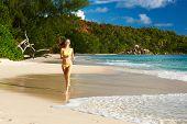 Woman in bikini running at tropical beach at Seychelles