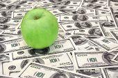 Green Apple On Heap Of Dollars