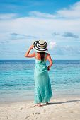 Beach vacation. Girl walking along a tropical beach in the Maldives.