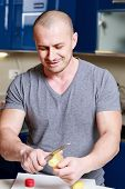 Handsome Man Who Ginger Peels On A Table In The Kitchen