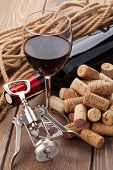 Glass of red wine, bottle, heap of corks and corkscrew on rustic wooden table