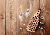Wine bottle shaped corks, glasses and corkscrew over rustic wooden table background. View from above with copy space