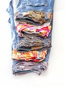 Women's jeans of various shades with motley silk belts on a show-window of shop