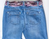 Women's jeans of various shades with motley silk belt