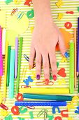 Multicolor female manicure with stationery on bright background