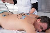 A Man Doing A Back Massage By Electrodes