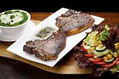 t bone steak with potato salad and vegetables