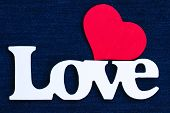 Love text with red heart on blue denim jean background
