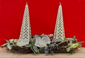 Pillars candle with  christmas decoration against red background