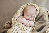 stock photo of newborn baby girl  - A newborn baby girl snuggled in a warm blanket cocoon selective focus with focus on face - JPG