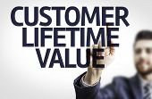 Business man pointing to transparent board with text: Customer Lifetime Value