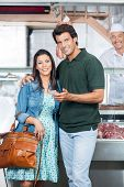 Portrait of loving mature couple in butchery