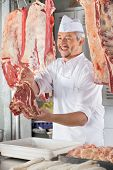 Happy male butcher giving raw meat at counter in shop