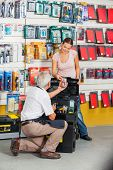 Full length of senior salesman assisting female customer in hardware store