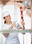 Happy mature female butcher cutting sausages at selling counter
