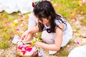 Wedding - flower child or bridesmaid in white dress and flower baskets