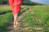 stock photo of walking away  - Bare feet of a young woman walking along a rural country road in the summer - JPG
