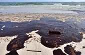 image of oil derrick  - Oil spill on beach with off shore oil rig in background - JPG
