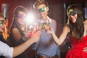 Friends in masquerade masks toasting with champagne at the nightclub