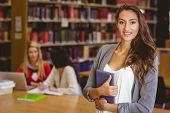 Pretty student holding tablet with classmates behind her in library